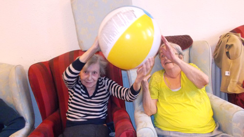 two female care clients enjoying a ball game activity with a larger group around them